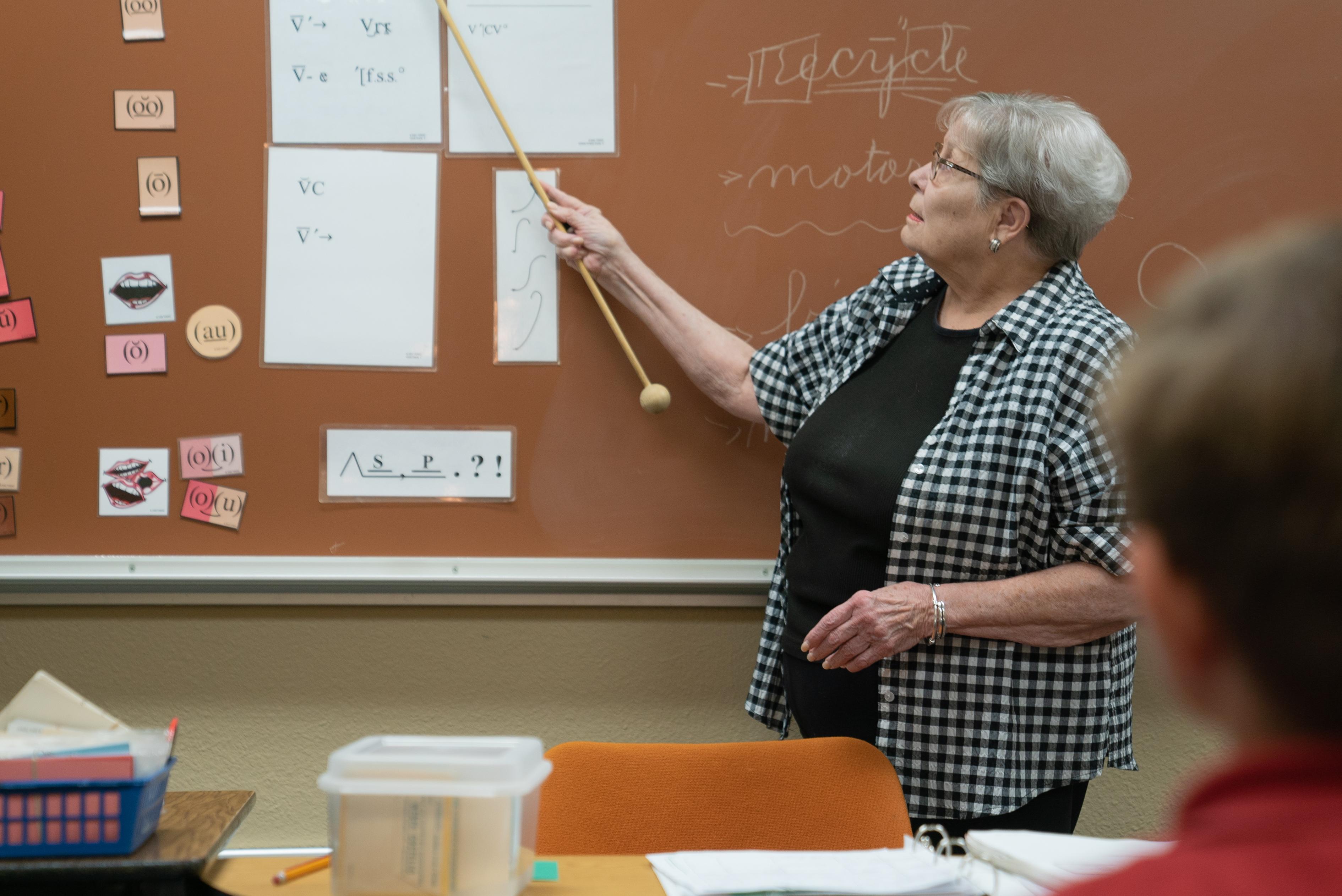 Dyslexia therapist pointing to chalkboard